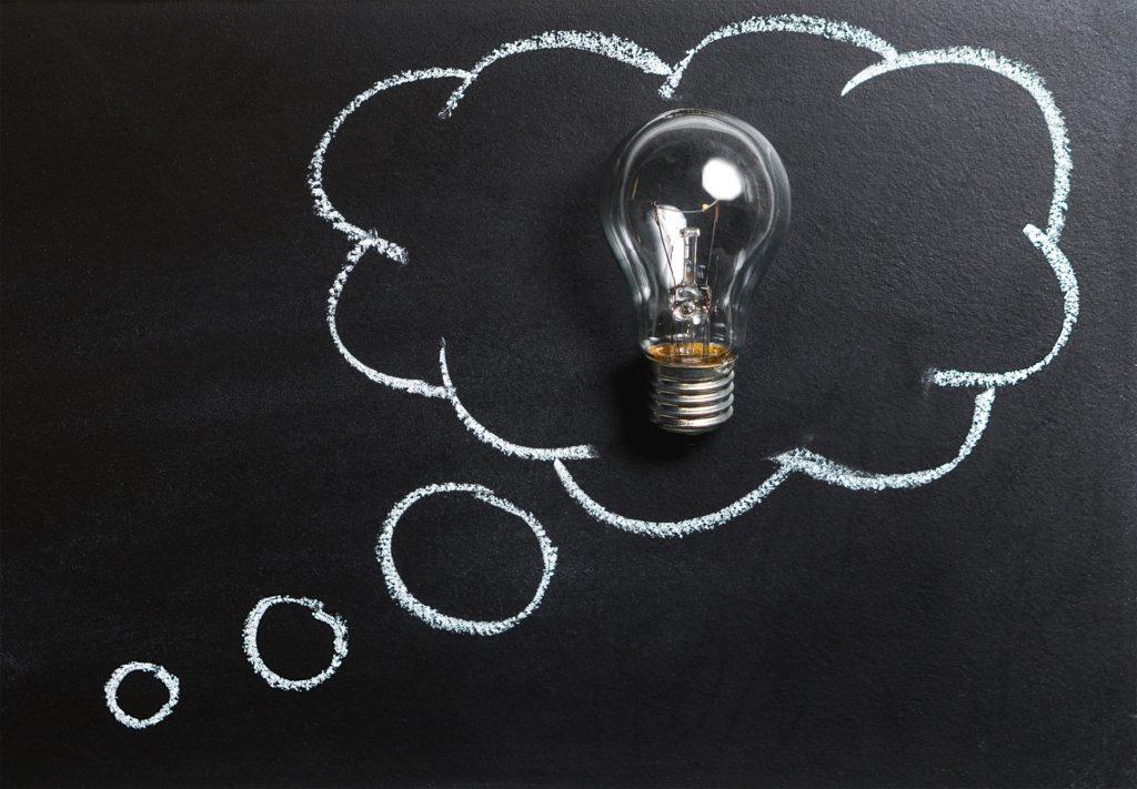 Glühbirne auf schwarzer Tafel mit Gedankenblase aus Kreide