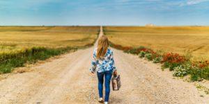 Frau mit Koffer am Anfang einer langen Straße
